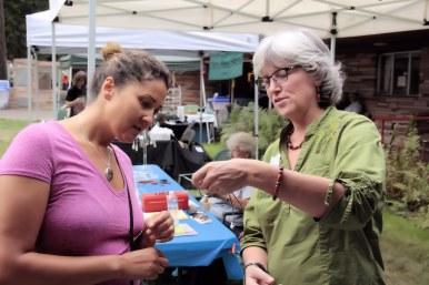 Vendor demonstrates precious stones to visitor.