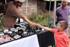 Vendor hands rock to child.
