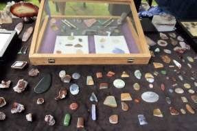 Polished rocks and minerals on display in vendor booth.